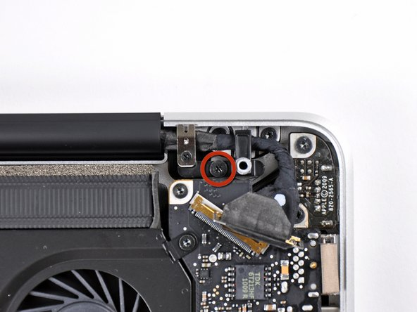 Remove the 8.6 mm Phillips screw securing the display data cable retainer to the upper case.