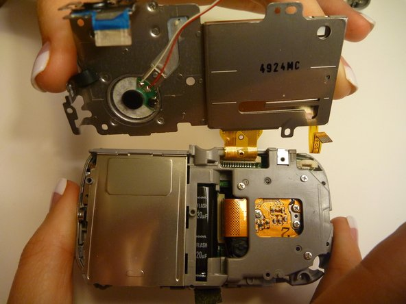 Lift the LCD screen so the thick yellow wiring is the only thing attaching the LCD screen to the camera.