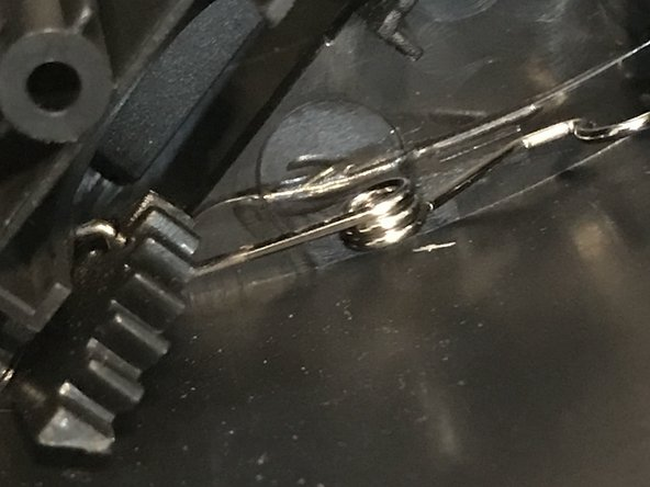 Remove the spring with a flat tip screwdriver.
