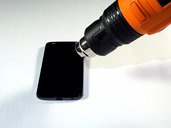 """Heat the edges of your Motorola Moto Z2 Play screen for two to three minutes with a heat gun. You adjust the heat gun to 85 degrees centigrade, and be careful not to hold the heat gun on one position for too long; to avoid damaging, or """"hotspotting"""" the LCD. The screen should be very warm, but not painful, to the touch. Reheat as necessary."""