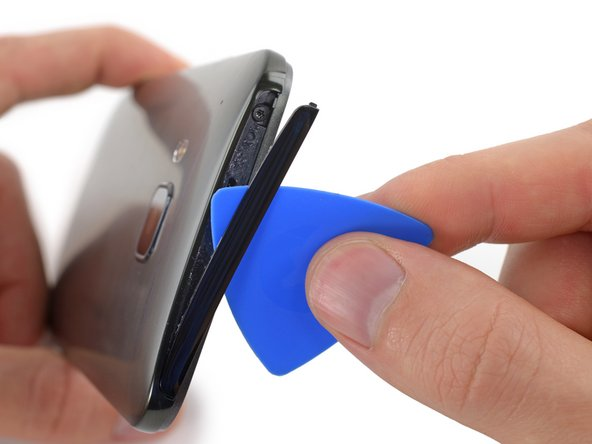 Using a plastic opening pick or a spudger, gently pry and remove the cover on top of the case.