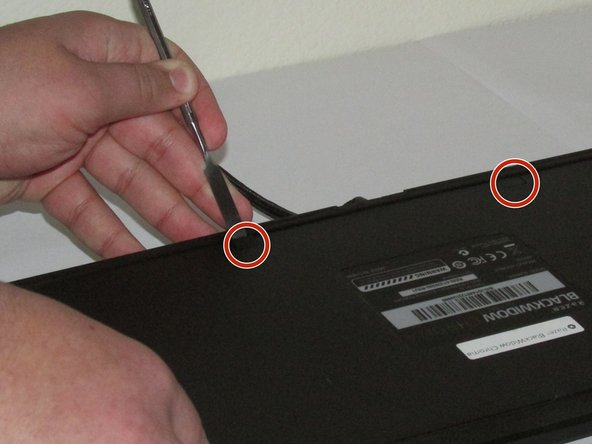 Using a metal spudger, gently remove the plastic tabs that are covering the two screws.