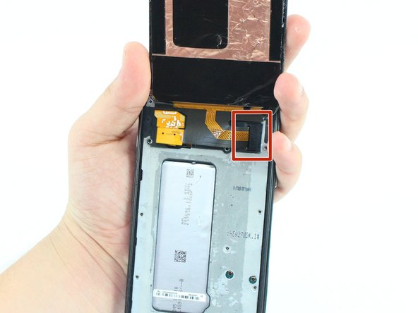 Once the glass is off, you will see a small clip covering the screen connection to the motherboard at the top of the phone. Use tweezers to grab the clip by the crease on its side and pull it out.