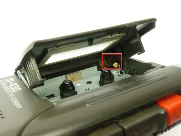 Using a spudger, apply pressure towards the back corner of the cassette compartment to the plastic tab directly behind the gold cone.