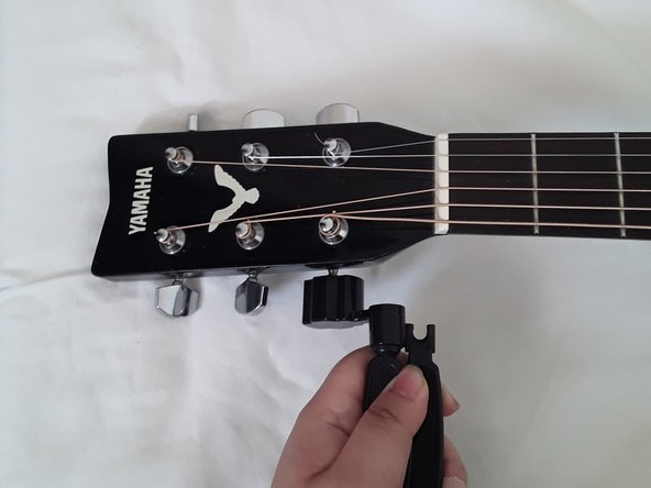 Turn the tuning peg clockwise using the All-In-1 Restringing Tool's peg winder to loosen the tension of the strings.