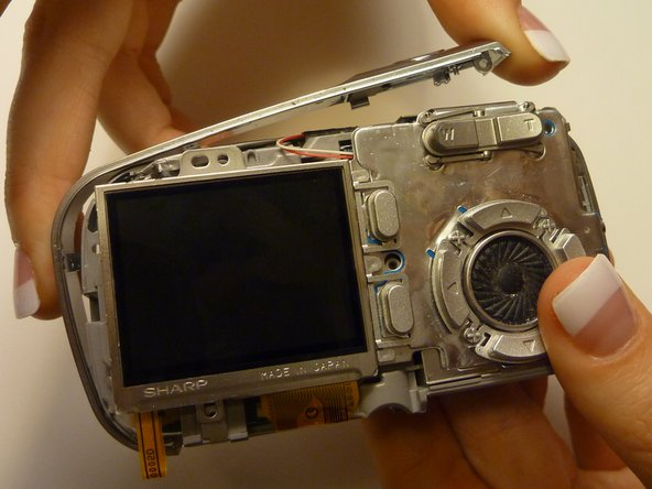 Remove the side pannel by sliding it off the body of the camera.
