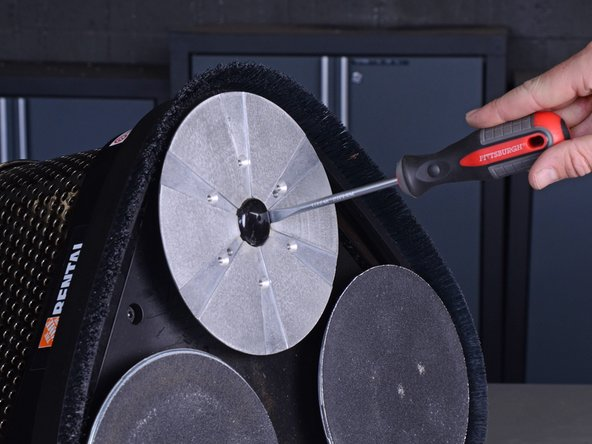 Use a flathead screwdriver to pry off and remove the rubber plug in the center of the sanding disc.