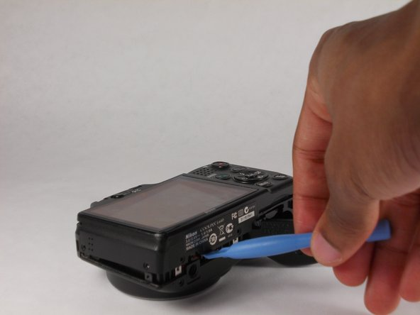 Separate the case using the plastic prying tool. This can be done by placing the tool in the position that is shown and in the position on the left side of the camera.