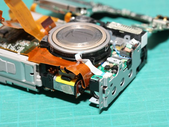 With the main logic board swung aside, the target of our repair is nearly visible! - the lens module...