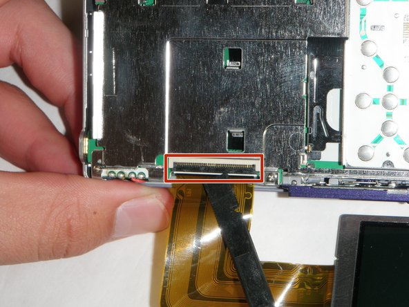 Using the spudger lift the black flap up to release the ribbon cable.