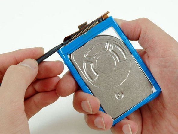 Use a spudger to carefully disconnect the orange ribbon cable from the hard drive.