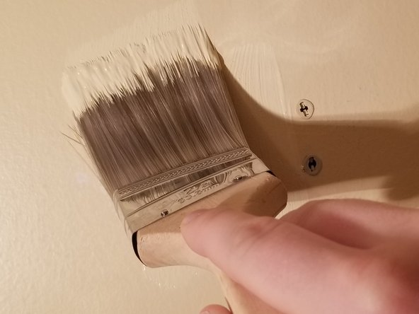 Use a brush and matching wall paint to coat the areas that were puttied and allow it to dry.