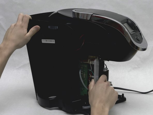 Remove the entire back exterior surrounding the Keurig by removing the latches connecting the back exterior to the silver frame on top. To do this, use the metal spudger to lift the latches up and out.