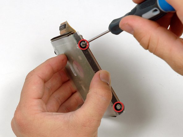 Remove the two silver Phillips screws and black rubber bumpers from either side of the hard drive (four sets of screws and bumpers total).