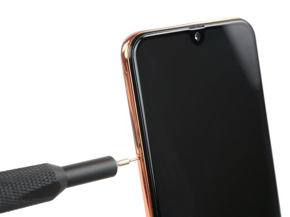 Insert a SIM card eject tool, a SIM eject bit or a straightened paper clip into the hole on the SIM tray located on the left side of the phone.