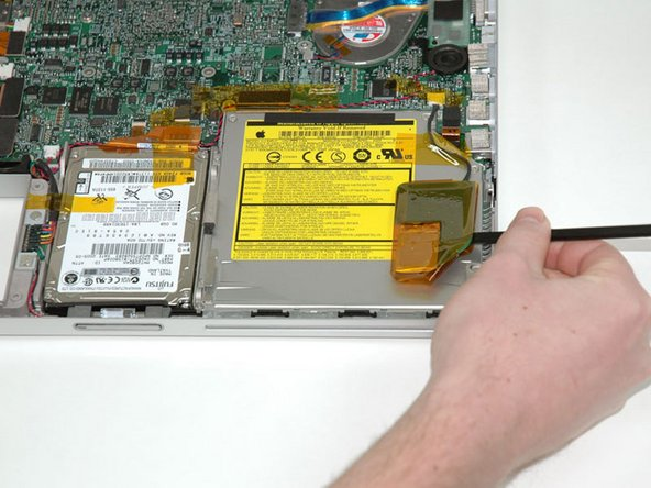 Use a spudger to pry up the PRAM battery from the optical drive.