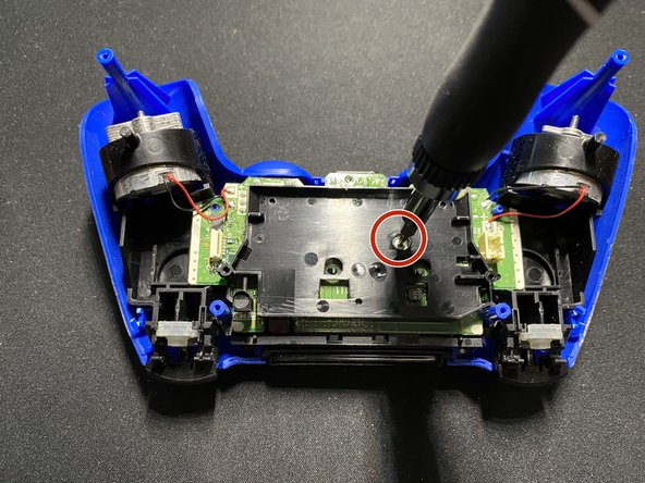 Remove the single screw from the black plate covering the motherboard using a Phillips #0 screwdriver.