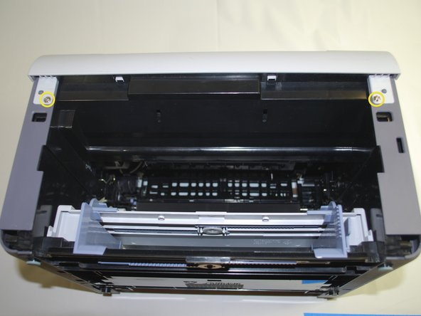 "Using a Phillips #2 screwdriver, remove the two 1"" screws on the front face of the printer."
