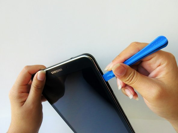 Continue prying the blue plastic opening tool along the perimeter of the tablet to separate the back plastic casing from the front assembly panel.
