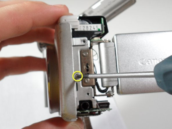 Unscrew the 2.4 mm long screw that holds on the front panel  underneath the side panel using the #00 screwdriver.