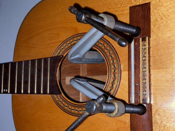 Use a C-clamp to gently clamp the bridge to the body of the guitar.