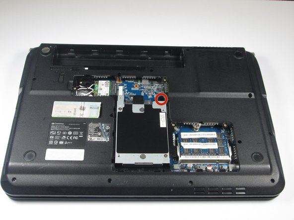 """Remove the 1/4"""" Phillips #0 screw located at the top right of the hard drive."""