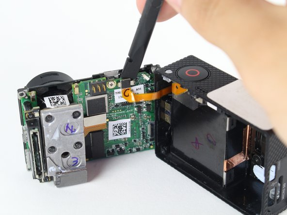Use the spudger to gently pry off the connector of the housing to the motherboard.