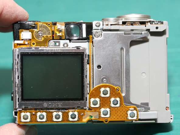 Here is the back of the camera without the shell. You can see the switch contacts on the flex circuit along the bottom. They're attached to the small metal plate that we'll remove in the next step...