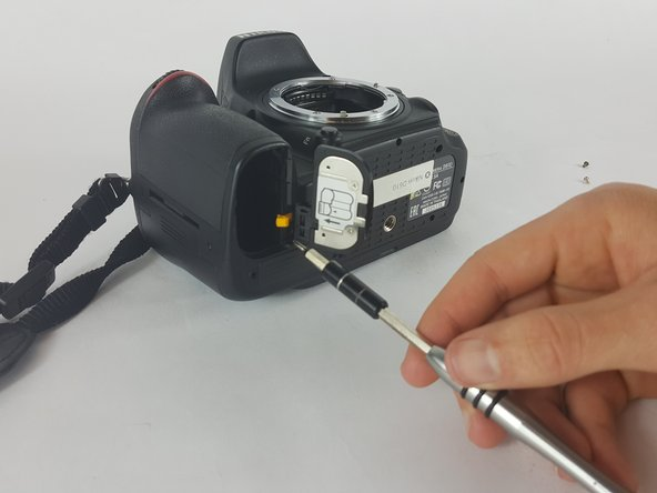 After removal of the battery. Pull the battery compartment door away from the lens.