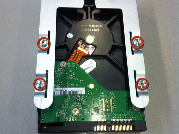 Remove your new hard drive from its packaging and use a phillips head screw drive to attach it to the bracket. Use the screws that are already included on the bracket.