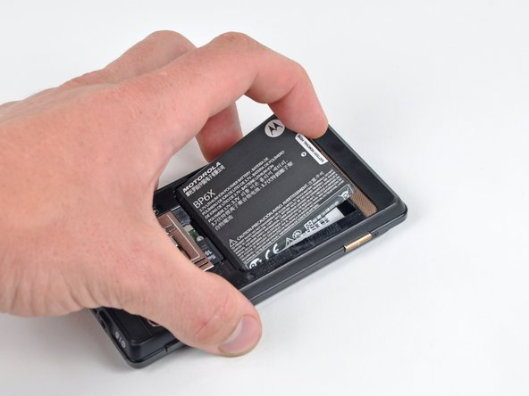 Grasp the upper left corner of the battery and lift it out of its housing.