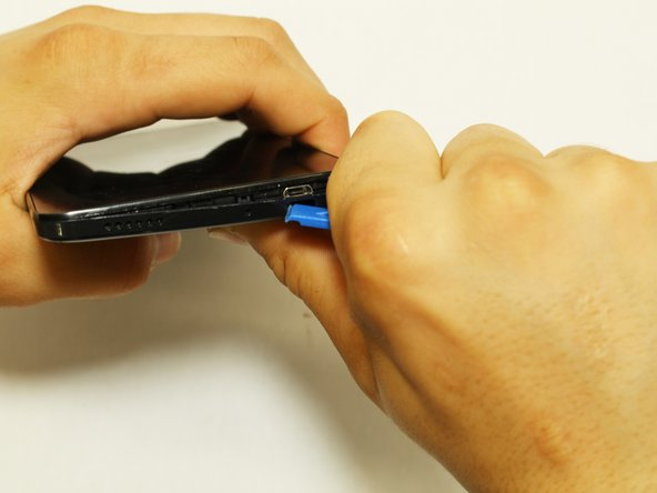 Make a thumbs-up and use it to grip the plastic opening tool with the flat end pointing in the direction of your thumb.