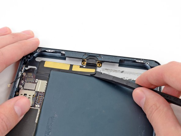 Slide the flat end of a spudger underneath the Lightning port cable, freeing it from the adhesive securing it to the rear case.