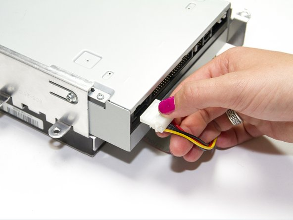 Unplug the power source from the optical drive by pinching the plastic base of the connector and wiggling it gently.