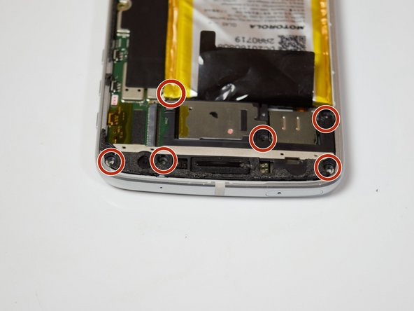 Remove the six 3mm T3 screws from the camera cover at the top of the phone.