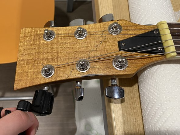 Loosen the guitar strings using a string winder.
