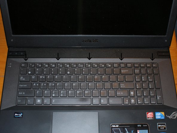 Here we have the keyboard.  It, too, must be removed.  The arrows point to the five retaining clips that keep the keyboard locked in place.