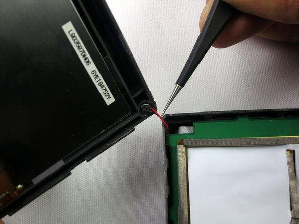 Using tweezers, gently lift the microphone from its resting position to fully separate the device into two parts.
