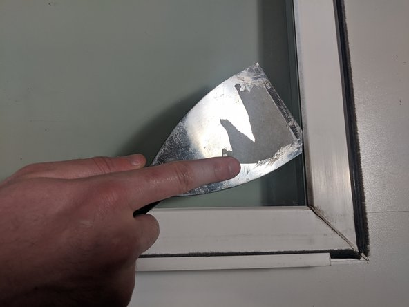 With the non-beveled putty knife, slip the edge of the knife between the frame and the pane itself.