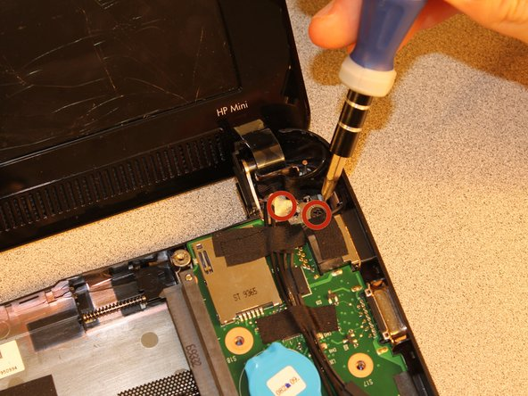 Remove the two 3.8mm PH1 screws with a Philips Head screw driver holding the right screen bracket in place.