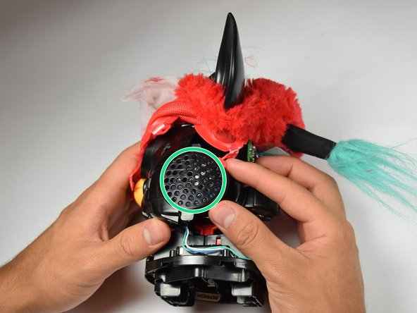 Orient Furby to where the mouth is facing left. Locate the speaker on the side of the device.