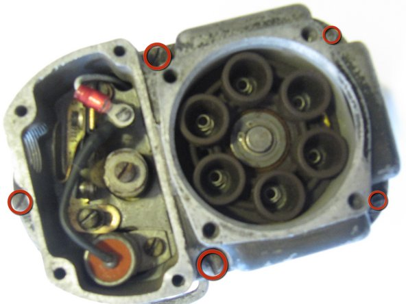 Use a #2 Flathead screw driver to remove the five screws on the body of the magneto, indicated by the red circles.