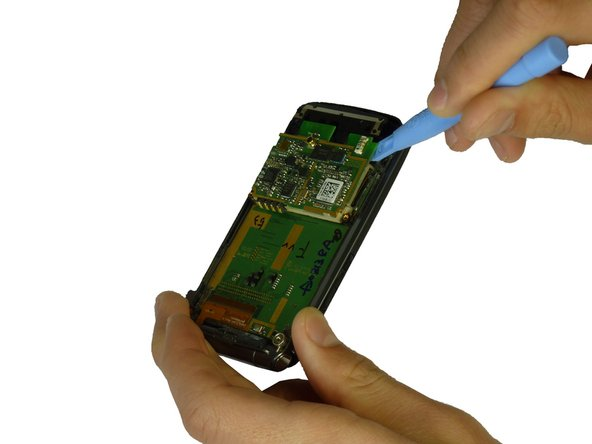 Use the spudger to lift the motherboard from the phone.