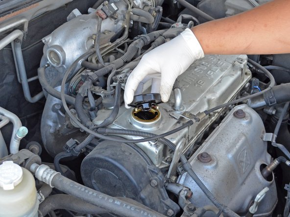 Remove the funnel and place the oil filler cap over the oil filler hole.