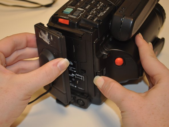 Holding battery device firmly between thumb and forefinger, apply pressure to the battery component, sliding the plastic to the left.