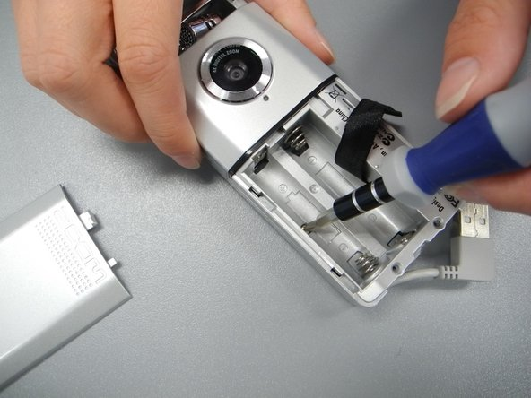 Remove the final screw from the bed of the battery compartment.