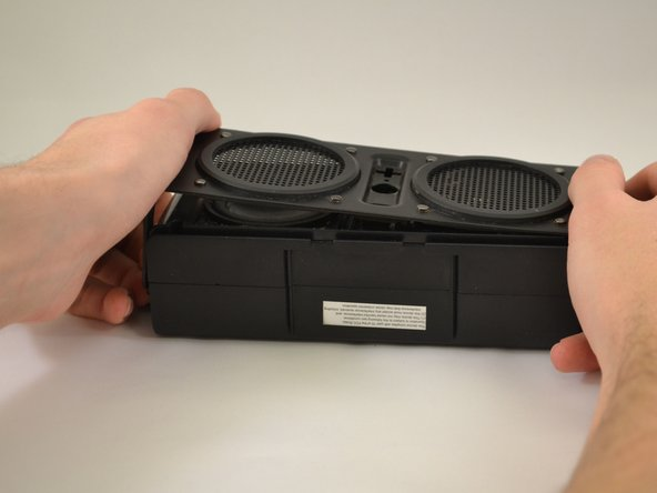 Gently pull the sides of the front plate outwards from the device.