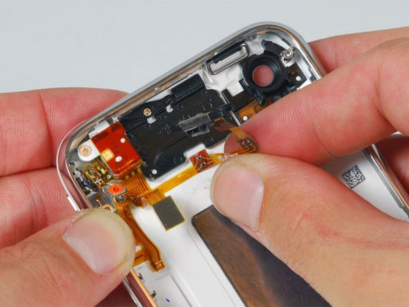 Carefully peel up the orange ribbon cable from the rear case.