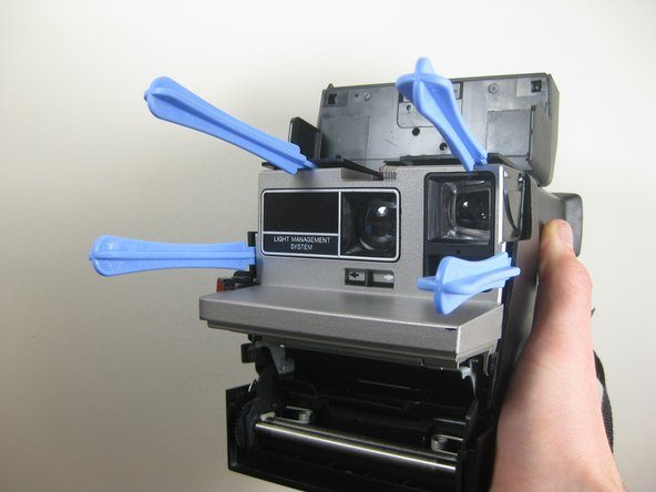 Use several plastic opening tools around the edges of the camera's body to separate it from the plastic frame.