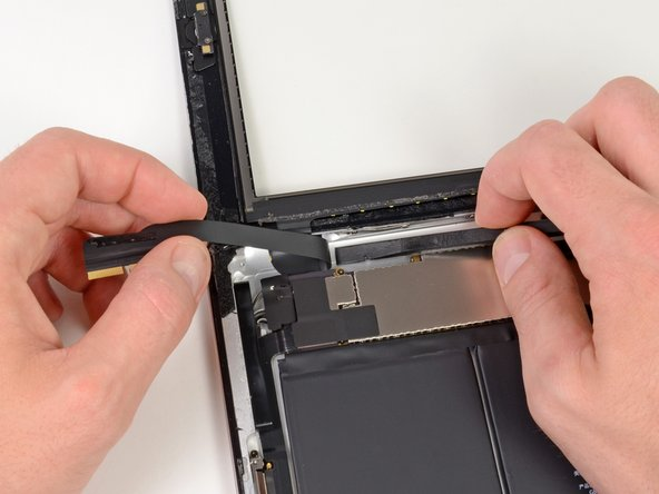 Peel back the digitizer ribbon cable and use the flat end of a spudger to release the adhesive securing the cable to the rear aluminum case.